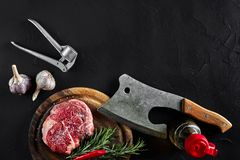 Piece of beef tenderloin, with ax for cutting and chopping meat, spices were cooking - rosemary, pepper, salt, garlic. Fresh raw meat. Beef. Piece of beef steak Royalty Free Stock Photo
