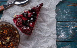 A piece of berry pie and a cup of tea on a wooden background Royalty Free Stock Photos