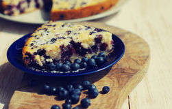Piece of bilberry pie on a blue plate and juicy berries of bilberry Stock Images