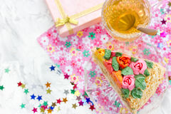 Piece of birthday cake, tea in cup, gift box and colorful confetti