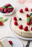 Piece of birthday cake with whole cake on white table royalty free stock image