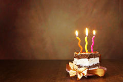Piece of birthday chocolate cake with burning candles Stock Photography