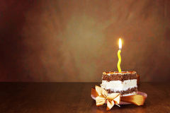 Piece of birthday chocolate cake with one burning candle Stock Photos