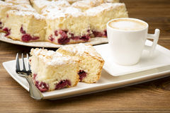 A  piece of biscuit with cherry and a cup of coffee on the wooden surface. Royalty Free Stock Photography