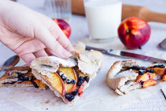 A piece of biscuit with peach and blueberry. In hand Royalty Free Stock Photos
