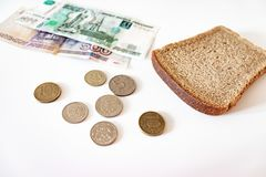 A piece of black bread, coins and paper rubles on the table. The concept of poverty, lack of money for food.  royalty free stock photography