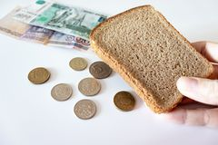 A piece of black bread in hand and coins and paper rubles on the table. The concept of poverty, lack of money for food.  royalty free stock photography