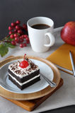 Piece of Black Forest Cake. With cup of coffee and notebook on background Stock Photos