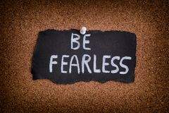 Piece of black paper with phrase Be Fearless Stock Images