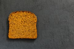 A piece of black rye bread on a black background.  stock photos