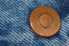 Piece of blue denim structure of the yellow button Royalty Free Stock Photos