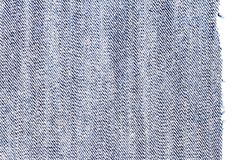 Piece of blue jeans fabric. Isolated on white background. Rough uneven edges. Denim pants torn. Wrong side of fabric royalty free stock image