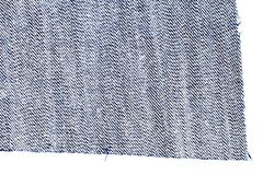 Piece of blue jeans fabric. Isolated on white background. Rough uneven edges. Denim pants torn. Wrong side of fabric royalty free stock images