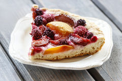 Piece of blueberry, peach and plum cake Royalty Free Stock Image
