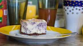 Piece of blueberry pie on a plate, glasses in the background royalty free stock images