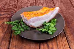 Piece of boiled smoked pork belly on dish with greens. Piece of boiled smoked pork belly with rind on the brown dish with greens on the wooden rustic table stock photography
