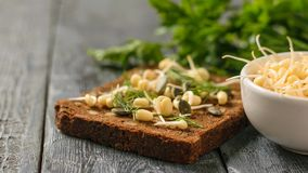 A piece of bread with bran and cereals and sprouted mung beans on a black table royalty free stock images