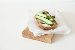A piece of bread with butter, salt with cucumber and greens lies on a wooden board on a white background. Stock Photos