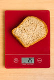 Piece of bread on a digital scale Stock Photo