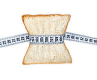 Piece of bread grasped by measuring tape Royalty Free Stock Photography