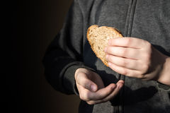 Piece of bread in hands Stock Photo