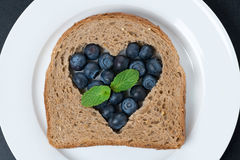 A piece of bread with the middle filled with fresh blueberries Royalty Free Stock Photography