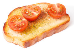Piece of bread with olive oil and tomatoes Stock Image