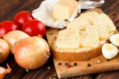 Piece of bread with ripened cheese on chopping board Royalty Free Stock Images