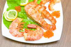 A piece of broiled fish, shrimp and red caviar on white plate cl Royalty Free Stock Photos