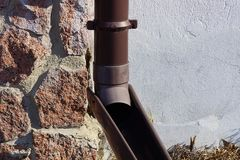 A piece of brown plastic drain pipe on the wall of a building stock photography