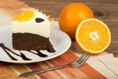 A piece of brownie cake with cream and oranges. A piece of brownie cake with cream and oranges on the wooden background Royalty Free Stock Photography