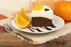 A piece of brownie cake with cream and oranges. A piece of brownie cake with cream and oranges on the wooden surface Stock Photo