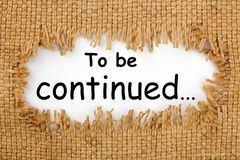 To Be Continued. Piece of burlap with hole with text `To be continued...`. Business concept royalty free stock photo