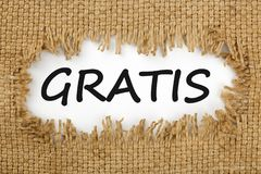 Gratis written in hole on the burlap. Piece of burlap with hole with word GRATIS. Business concept royalty free stock images