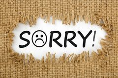 Sorry with sad smiley face. Piece of burlap with hole with word SORRY. Sad smiley face stock photography