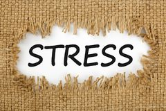 Stress written in hole on the burlap. Piece of burlap with hole with word STRESS. Business concept. Top view Stock Photos