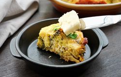 Piece of butter is added to a slice of broccoli bake. Piece of butter is added on top of a slice of broccoli, leek, cauliflower, cheese bake.  Ketogenic low-carb stock photos
