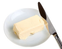 Piece of butter on a saucer and knife Royalty Free Stock Image