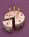 Piece of cake. Wooden birthday cake. A symbol of something whole divided into pieces Royalty Free Stock Image