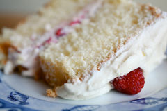 Piece of Cake. Close up of a piece of delicious sponge and cream cake on a plate topped with a juicy raspberry Royalty Free Stock Image