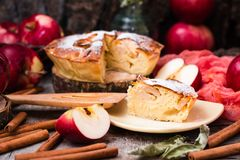 Piece of cake with apples on a saucer. Wooden table Stock Images