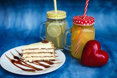 A piece of cake beautifully served. In the background lemonade in jars and a red heart stock image