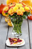 Piece of cake and bouquet of orange roses. Piece of cake and huge bouquet of orange roses on wooden table. Ripe pumpkins and rowan berry in the background Stock Image