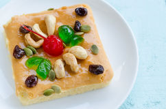 Piece of cake with cashew nut, cherry, jelly and raisin. Stock Photography