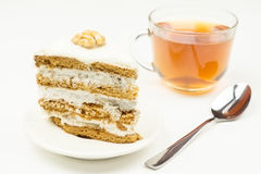 Piece of cake with cream, teaspoon,  Cup with tea on white backg. Piece of cake with cream, teaspoon, glass Cup with tea on white background Stock Photo