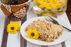 Piece of cake with crumbs, tea and yellow flowers on white woode Royalty Free Stock Photos