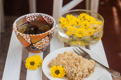 Piece of cake with crumbs, tea and yellow flowers on white woode Royalty Free Stock Images