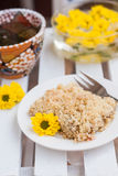 Piece of cake with crumbs, tea and yellow flowers on white woode Royalty Free Stock Photo