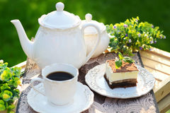A piece of cake with a cup of coffee. A piece of cake with a cup of black coffee Stock Photos