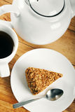Piece of cake and cup of coffee on wooden table Royalty Free Stock Photos